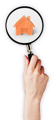 Hand holding a magnifying glass over an orange house